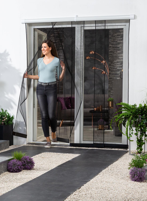 """Eine Frau geht vom Wohnraum aus durch die geöffnete Terrassentüre und dem von ihr zur Seite geschobenen Schiebe-Lamellenvorhang """"VARIO"""" in schwarz nach draußen."""