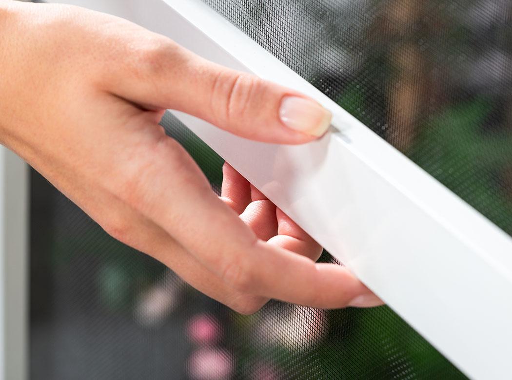 Eine Hand befindet sich am weißen Mittelprofil der Insektenschutztür flächenbündig.