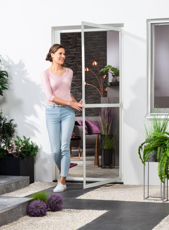 Eine Frau geht vom Wohnraum aus durch die von ihr geöffnete Insektenschutztür flächenbündig in weiß nach draußen.