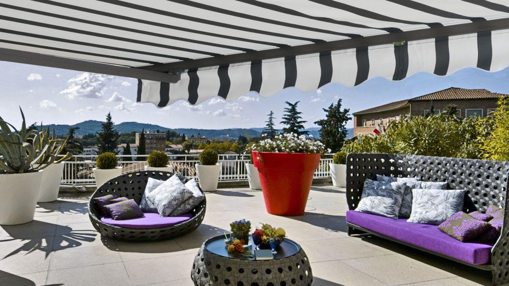 Die Gelenkarmmarkise in weiß mit anthrazitfarbenen Streifen hängt über einer sonnenbeschienen,möblierten Dachterasse und wirft einen Schatten.
