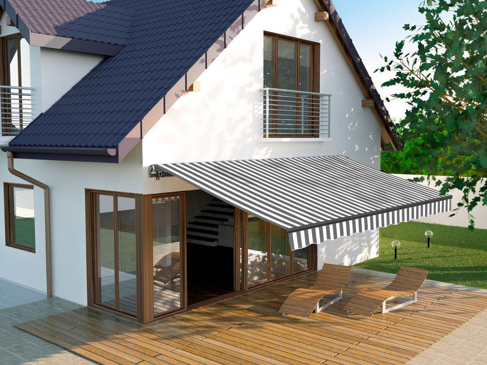Seitenansicht eines Hauses mit Terrasse. Die Markise ist über der Terrasse befestigt und ausgefahren. Sie wirft einen Schatten über der Terrasse.