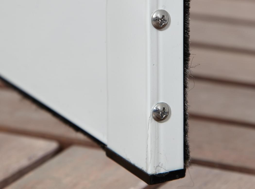 Fliegengitter, Insektenschutz Türbausatz Master Slim, in Rahmenfarbe weiss. Detailansicht der Verschraubung am Trittschutzprofil