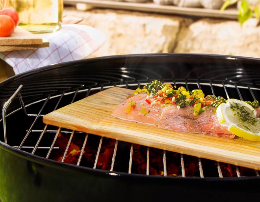 Grillbretter aus Zedernholz auf einem Grillrost liegend mit marniertem Fisch