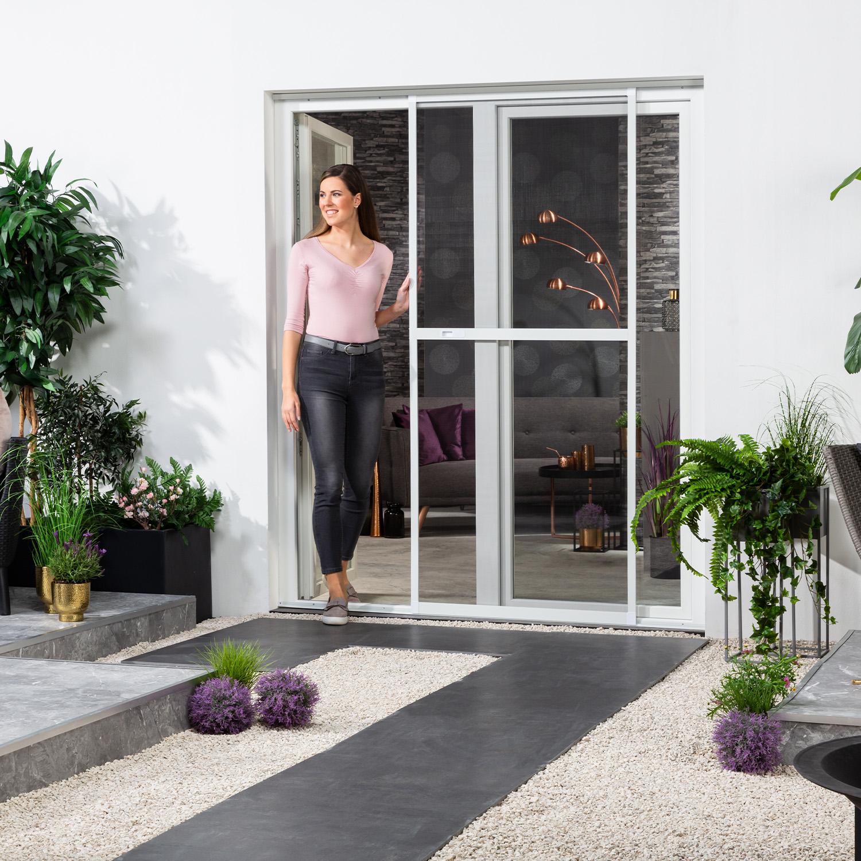 """Eine Frau geht aus dem Wohnraum auf die Terrasse. Dabei schiebt sie die Doppelschiebetüre """"COMFORT"""" zur Seite."""