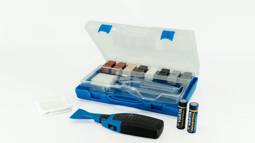 Ein geöffneter blauer Koffer, der das Fliesen-Reparatur-Set beeinhaltet. Zu sehen sind acht verschiedenfarbige Wachsstangen, zwei Batterien, Reinigungstuch, ein Schleifschwamm und ein Wachsschmelzer.