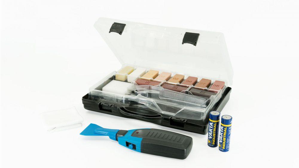 Ein geöffneter schwarzer Koffer, der das Laminat-/Parkett-Reparatur-Set beeinhaltet. Zu sehen sind elf verschiedenfarbige Wachsstangen, zwei Batterien, Reinigungstuch, ein Schleifschwamm und ein Wachsschmelzer.